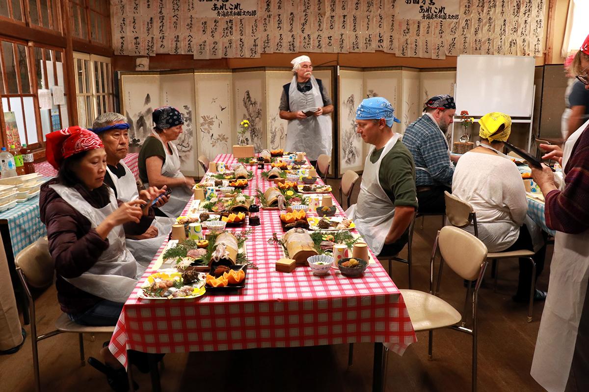 ▲「魚さばき体験」の後の食事風景。さばいた魚だけでなく、地元の食材をふんだんに使った料理もたくさん振舞われる。